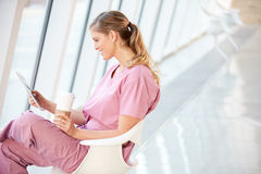 Female Nurse Using Digital Tablet On Coffee Break In Hospital Royalty Free Stock Photos