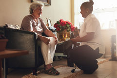 Female nurse visiting senior patient for checking blood pressure. Senior women sitting on a chair at home with female caregiver holding blood pressure gauge royalty free stock images