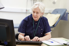Female Nurse Working At Desk In Office Stock Photo