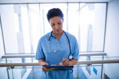 Female nurse writing in clipboard in corridor Royalty Free Stock Image