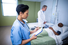 Female nurse writing on clipboard during visit in ward. Of hospital Stock Images