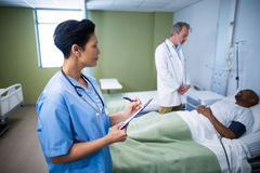 Female nurse writing on clipboard during visit in ward. Of hospital Stock Photo