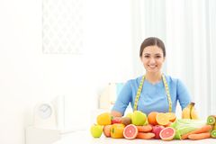 Female nutritionist with different fruits and vegetables. At desk Royalty Free Stock Photos