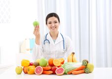 Female nutritionist with different fruits and vegetables. At desk stock image