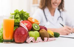 Female nutritionist doctor writing vegetable diet plan stock images