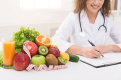 Female nutritionist doctor writing vegetable diet plan stock photo