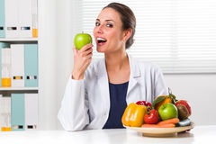 Female nutritionist eating a Green Apple in her office. Smiling Female nutritionist eating a Green Apple in her office and showing healthy vegetables and fruits royalty free stock photo