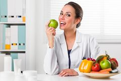 Female nutritionist eating a Green Apple in her office. Smiling Female nutritionist eating a Green Apple in her office and showing healthy vegetables and fruits Royalty Free Stock Images
