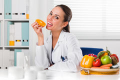 Female nutritionist eating an Orange Slice in her office. Smiling Female nutritionist eating an Orange Slice in her office and showing healthy vegetables and Royalty Free Stock Images