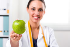 Female nutritionist giving a Green Apple. Smiling Female nutritionist with tape measure around her neck offering a Green Apple in her office; Healthcare and diet Royalty Free Stock Photo