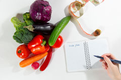 Female nutritionist hand writing diet plan. In notebook against fresh vegetable composition, white background, top view. Diet nutrition advertising. Healthy Royalty Free Stock Photo