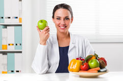 Female nutritionist holding a green apple. Smiling Female nutritionist holding a green apple and showing healthy vegetables and fruits in her office; Healthcare Royalty Free Stock Image