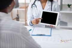 Female nutritionist showing empty digital tablet screen in office