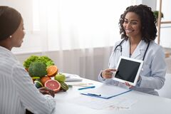 Female nutritionist using digital tablet in office, making patient`s anamnesis