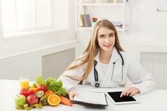 Female nutritionist working on digital tablet. In office. Beautiful woman dietitian typing, counting calories or writing diet plan, copy space. Healthy eating Stock Images