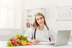 Female nutritionist working on laptop. In office, close up. Beautiful woman dietitian typing, counting calories or writing diet plan, copy space. Healthy eating Royalty Free Stock Images