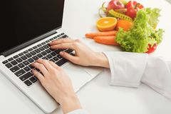 Female nutritionist working on laptop. In office, close up. Hands of woman dietitian typing, counting calories or writing diet plan, copy space Stock Images
