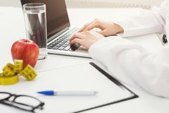 Female nutritionist working on laptop. In office, close up. Hands of woman dietitian typing, counting calories or writing diet plan, copy space Stock Image