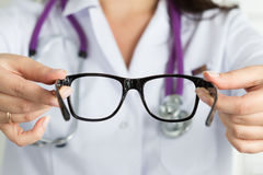 Female oculist doctor hands giving pair of glasses. Good vision. Female oculist doctor hands giving pair of black glasses to patient. Eyesight correction Stock Photography