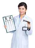 Female oculist holding eyechart and glasses Royalty Free Stock Photo