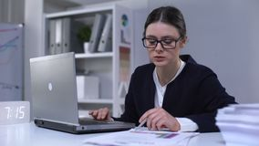 Female office employee looking through information in laptop and documents, work. Stock footage stock footage