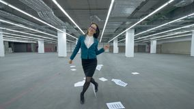 Female office manager is walking along the hall and starts fooling around. 4K stock video footage