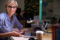 Female Office Worker With Coffee At Desk Working Late Stock Images
