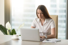 Female office worker doing everyday work routine. Diligent female office worker doing everyday work routine. Attentive woman sitting at desk and looking at Royalty Free Stock Image