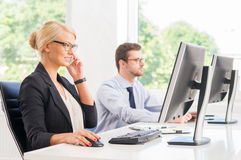 Female office worker in formalwear with her colleague Stock Images