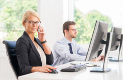 Female office worker in formalwear with her colleague Royalty Free Stock Photo