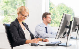 Female office worker in formalwear with her colleague Stock Photos