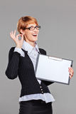 Female office worker gesturing perfect and holding a clipboard. On grey Stock Images