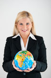 Female office worker with globe. Picture of a young friendly beautiful female office worker in a suit holding a globe stock image