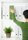 Female office worker with green folder. Female office worker choosing green folder with recycling symbol Royalty Free Stock Photos