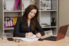 Female office worker grinning writing in a notebook for your desktop Royalty Free Stock Image