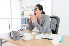 Female office worker having nose allergy problem. And feeling unwell sneezing in working office during season changing time stock image