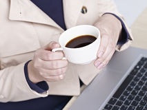 Female office worker holding a cup of coffee Royalty Free Stock Photo