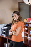 Female office worker, Indian ethnicity. Standing in mailroom with office equipment Royalty Free Stock Photo