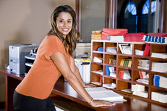 Female office worker, Indian ethnicity. Standing in mailroom with office equipment Stock Photography