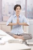 Female office worker meditating at work. Landline phone put aside in skyscraper office, woman in focus meditating with closed eyes at work Stock Photos