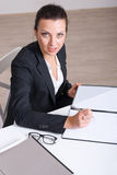 Female office worker signs documents sitting at a table Stock Photo