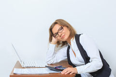 Female office worker sits at her desk and look Royalty Free Stock Image