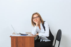 Female office worker sits at her desk and look Stock Photos