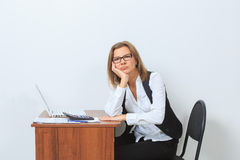 Female office worker sits at her desk and look Stock Photo