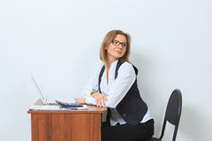 Female office worker sits at her desk and look Royalty Free Stock Photo