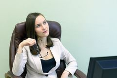 Female office worker sits in a leather chair in front of a computer and thinks.  Royalty Free Stock Images