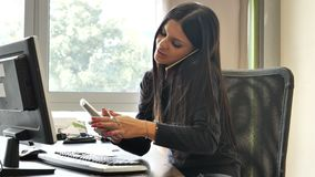 Female office worker sitting at desk busy with two phones. Serious attractive young businesswoman or office worker sitting at desk in office busy talking on stock footage