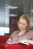 Female Office Worker Sitting On Sofa Royalty Free Stock Photos