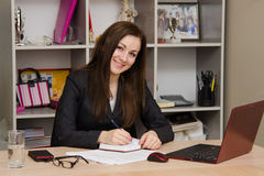 Female office worker with a smile, writing in notebook Royalty Free Stock Images