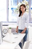 Female office worker standing by desk smiling Stock Images
